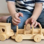 Fából készül vonattal játszó kisfiú (Fotó: Freepik)